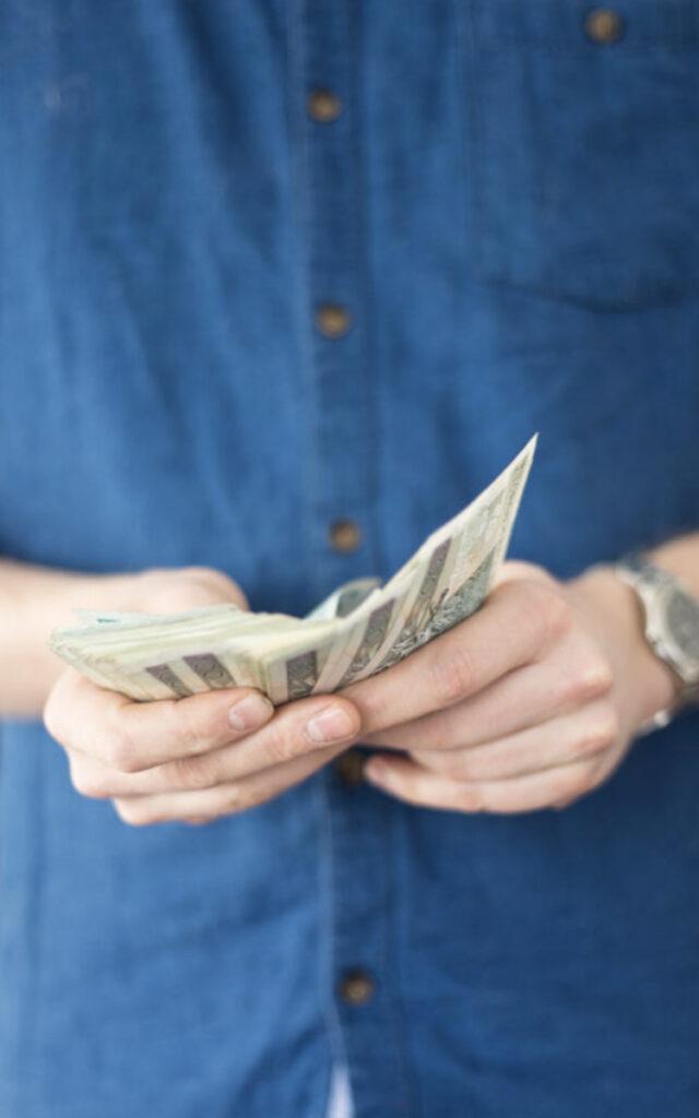 człowiek z pieniędzmi w rękach