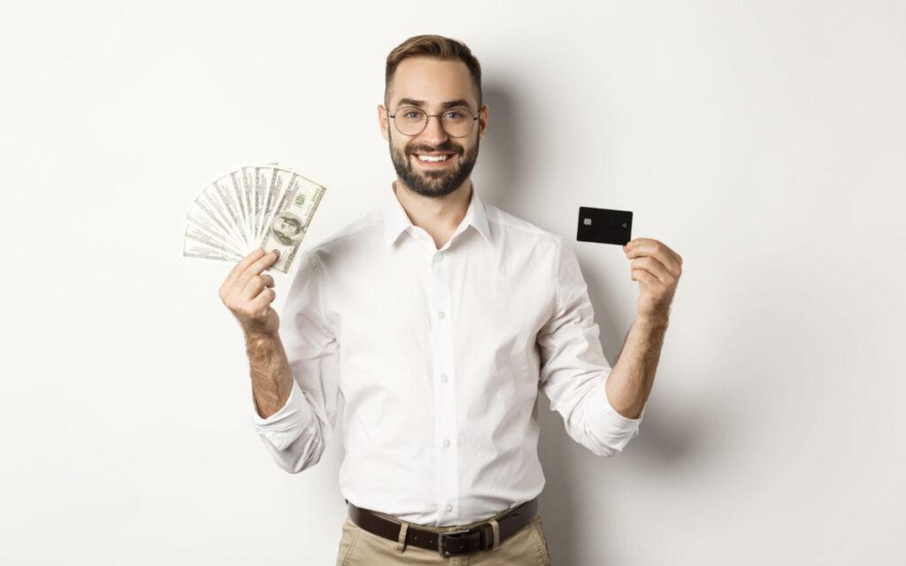 mężczyzna uśmiechający się z pieniędzmi i kartą kredytową w rękach
