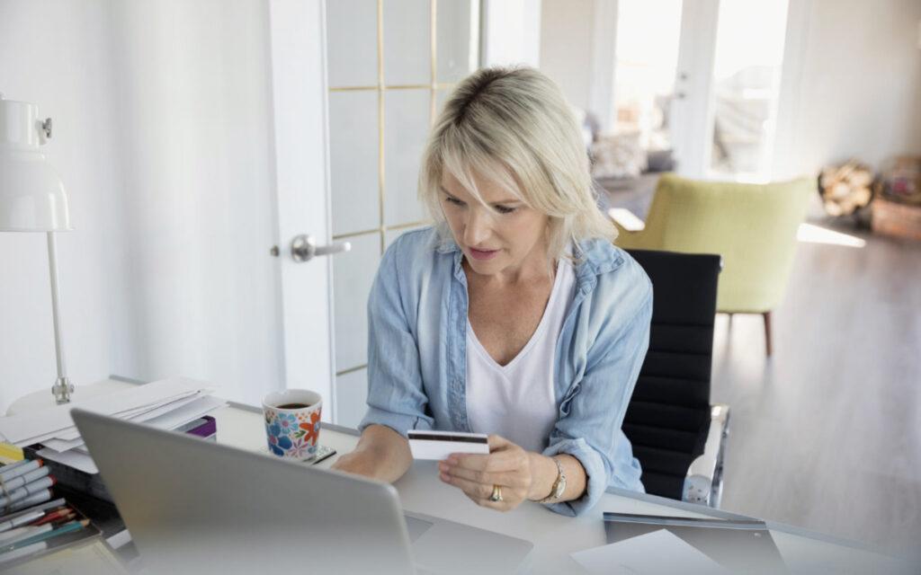 kobieta w salonie za laptopem z kartą kredytową
