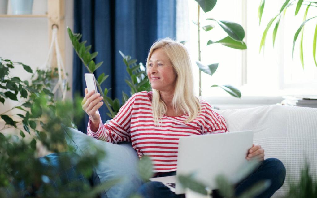 dorosła kobieta z telefonem komórkowym i laptopem na kanapie