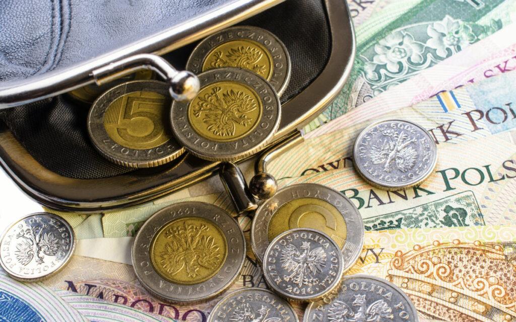banknoty i monety euro obok portfela