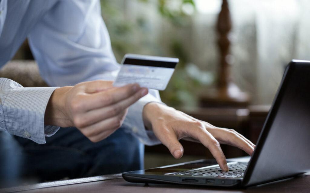 męskie dłonie, laptop, karta kredytowa